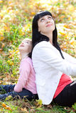 Young mother and her daughter looking up in the autumn Stock Images