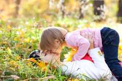 Young mother and her daughter lying on the autumn leav Royalty Free Stock Images