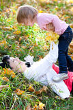 Young mother and her daughter lying on the autumn leav Stock Photography