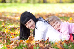 Young mother and her daughter lying on the autumn leav Royalty Free Stock Image