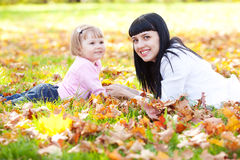 Young mother and her daughter lying on the autumn leav Royalty Free Stock Photos
