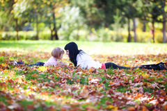 Young mother and her daughter lying on the autumn leav Royalty Free Stock Photo