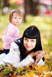 Young mother and her daughter lying on the autumn leav Stock Image