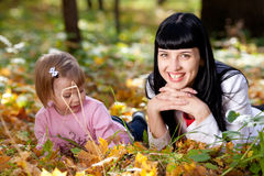 Young mother and her daughter lying on the autumn leav Stock Photo