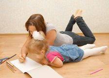 Young mother with her daughter lying on the floor Stock Image