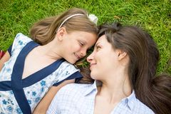 Young mother and her daughter lying on the grass Royalty Free Stock Photo