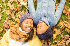 Young mother with her daughter lying in leaves Stock Photo