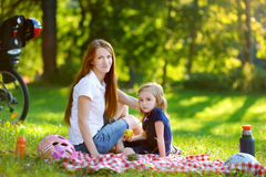 Young mother and her daughter picnicking Stock Images
