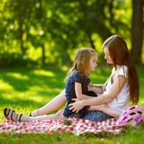 Young mother and her daughter picnicking Royalty Free Stock Photos