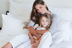 Young mother and her daughter posing on a bed Royalty Free Stock Photo