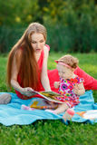 Young mother with her daughter read book sitting on plaid Stock Images