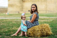 A young mother with her daughter sits on a straw near the fortress stock image