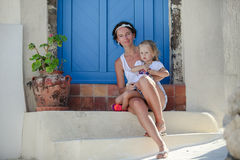 Young mother and her daughter sitting on doorstep. Of old house in Emporio village, Santorini, Greece. This image has attached release Royalty Free Stock Photo