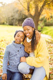 Young mother with her daughter sitting in leaves Stock Photos