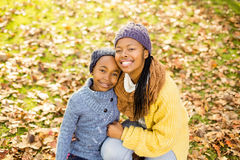 Young mother with her daughter sitting in leaves Royalty Free Stock Photography