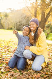 Young mother with her daughter sitting in leaves Royalty Free Stock Image