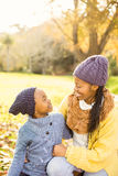 Young mother with her daughter sitting in leaves Stock Images