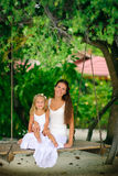 Young mother and her daughter swinging at tropic Royalty Free Stock Images