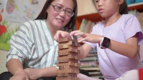 Young mother and her daughter try to build wooden block tower.