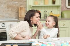 A young mother and her daughter trying cookies stock images