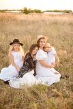A young mother with her daughters and an aunt with blond hair in white dresses at sunset in the summer in a field of countryside. Several girls from the same stock image