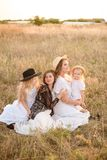 A young mother with her daughters and an aunt with blond hair in white dresses at sunset in the summer in a field of countryside. Several girls from the same stock photos