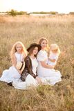 A young mother with her daughters and an aunt with blond hair in white dresses at sunset in the summer in a field of countryside. Several girls from the same stock photography