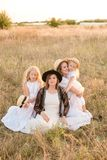 A young mother with her daughters and an aunt with blond hair in white dresses at sunset in the summer in a field of countryside. Several girls from the same stock photo