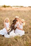 A young mother with her daughters and an aunt with blond hair in white dresses at sunset in the summer in a field of countryside. Several girls from the same royalty free stock photography