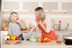 Young mother and her daughters eating tomatos stock image