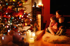Young mother and her daughters by a fireplace Royalty Free Stock Images
