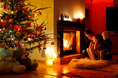 Young mother and her daughters by a fireplace Stock Photos