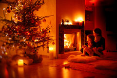 Young mother and her daughters by a fireplace Royalty Free Stock Photography