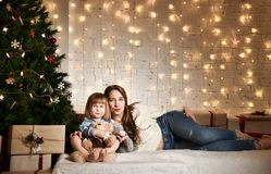 Young mother and her daughters near the Christmas tree. royalty free stock photos