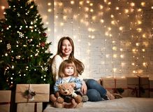 Young mother and her daughters near the Christmas tree. stock photo