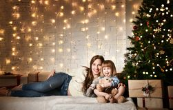 Young mother and her daughters near the Christmas tree. stock photography