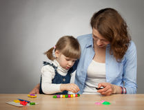 Young mother and her dauther modelling with plasticine Stock Photography