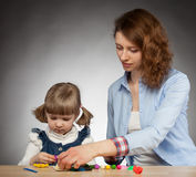 Young mother and her dauther modelling with plasticine Stock Photo