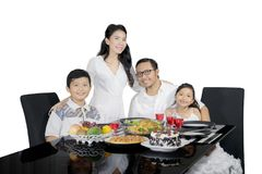 Young mother with her family at dinner time Royalty Free Stock Photography