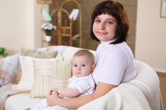 A young mother with her infant baby at home Stock Images