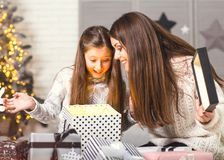 Young mother and her ittle daughters opening a magical Christmas Royalty Free Stock Images