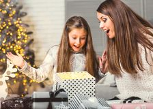 Young mother and her ittle daughters opening a magical Christmas Royalty Free Stock Photography
