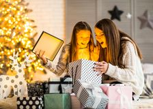 Young mother and her ittle daughters opening a magical Christmas Stock Photos