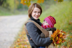 Young mother with her little baby. In a carrier Stock Photography