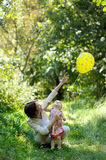 Young mother and her little baby with a balloon. Young mother and her little baby looking at the yellow balloon Royalty Free Stock Photo