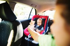 Young mother with her little baby boy in the car. Young mother with her little son in the car. Baby boy sitting in a car seat, unrecognizable women giving him a Stock Photos