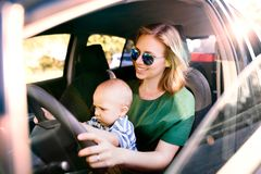 Young mother with her little baby boy in the car. Young mother with her little son in the car. A women and baby boy pretending to be driving Stock Photos