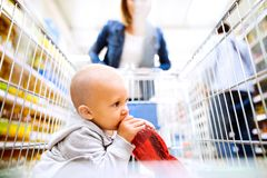 Young mother with her little baby boy at the supermarket. Royalty Free Stock Photo