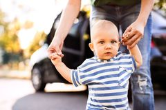 Young mother with her little baby boy walking by the car. Unrecognizable young mother helping her little baby boy walk. First steps, near a car Stock Images