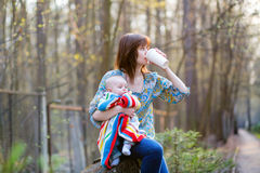 Young mother with her little baby, drinking coffee Stock Photo